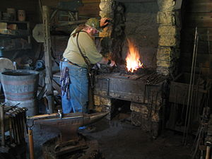 John Deere House and Shop - A modern-day blacksmith tends to the fire in the forge in the replica blacksmith shop.