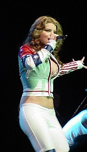 A woman is performing a song over the stage. She wears a white jacket and pants.