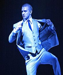 A man with blue light being cast down upon him. He is wearing a suit, including a vest and tie, and his hands are placed on his jacket.