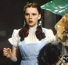 A color screenshot of a woman in blue overalls looking to her right while holding a dog in her left hand and raising her right to equal height.
