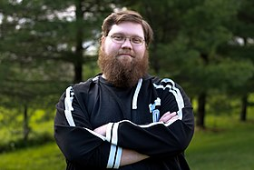 Justin Knapp—a Caucasian male with brown hair and a bushy beard—stands with his arms folded