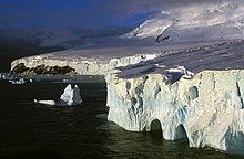 Image of barren, glacial coastline surrounded by ice cliffs and bergs