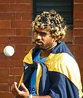 Lasith Malinga tossing a cricket ball during practice.