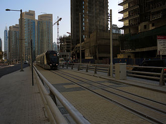 Dubai Tram - Tram on test run in November 2014. Note safety barriers each side of tracks.