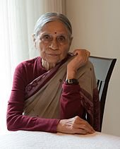 A photograph of an old woman sitting on a chair wearing sari with right hand kept on the table
