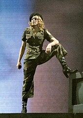 Madonna with her heel up, wearing a military uniform, posing onstage