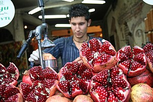 English: A worker preparing fresh pomegranate ...