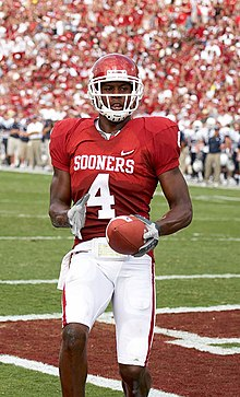 An American football player wearing a red helmet, red jersey (number 4) and white pants holds a football after scoring a touchdown in a game.
