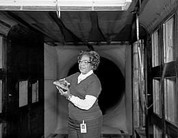 Black and white photograph of Mary Jackson holding a model in a wind tunnel