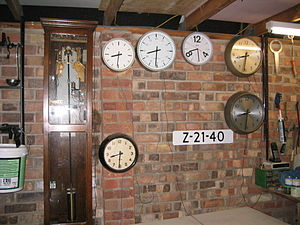 Master clock - Master clock (at left) driving several slave clocks in an enthusiast's garage. Note that the third one from the left at the top is a radio-controlled radio clock for reference.