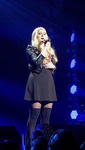 Meghan Trainor performing on stage with blue stage lighting shining upon her