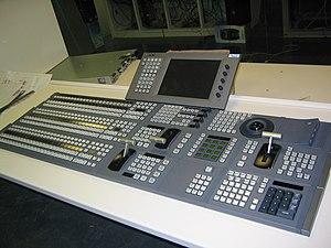 Consola de una mesa de vídeo Sony con dos bancos.