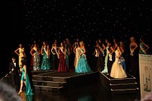 A photograph of a large group of women all wearing differently coloured dresses and standing on a stage in front of a black background