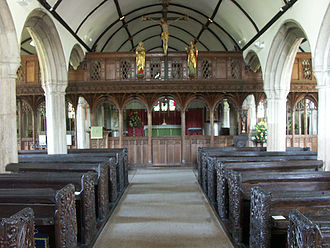 Rood screen - A rood screen in an Anglican parish church. The 15th-century rood screen of St Mellanus, Mullion, Cornwall, restored with rood figures and loft by F. C. Eden in 1925.
