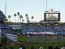 Twee rijen mannen staan op een honkbalveld met honkbalpetten over hun hart.  Rechts van de afbeelding staat een rij mannen in grijze honkbaluniformen en rode petten, links staan mannen in witte honkbaluniformen en blauwe petten.  De tribunes staan vol met publieksleden en andere mensen staan in het outfield, gezien op de achtergrond.