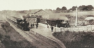 North Wales Narrow Gauge Railways - Dinas station in 1883. A NWNGR train with Beddgelert and a LNWR train are waiting on the platforms.