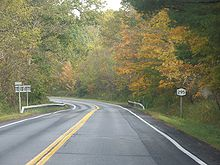 A highway cutting through a forest. Fall foliage is beginning to emerge.