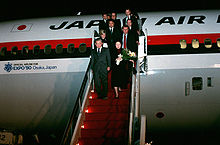 Japan Prime Minister Noboru Takeshita and 11 others deplane on steps in red colour, from a Japan Air Lines DC-10 marked with an Official Airline for Expo '90 Osaka, Japan logo and text