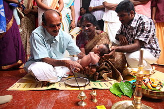 Naming ceremony - A baby's paternal grandfather in Kerala performing Nool Kettu by tying a black string on the waist of the child