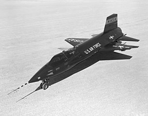 Black rocket aircraft with stubby wings and short vertical stabilizers above and below tail unit