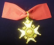 Photograph from above of a badge of a Companion of the Order of the Bath lying on a navy blue fabric.