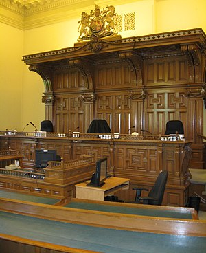 Court of Appeal for Ontario - An OCA courtroom at Osgoode Hall. Over the dais is the Royal Arms of the United Kingdom, which until 1931 was the Royal Arms for general purposes throughout the British Empire. The Statute of Westminster, 1931 effectively elevated the Royal Arms of Canada to the position of the Queen's Royal Arms for general purposes across Canada, which is why the Canadian Coat of Arms are now used by the court to represent the Canadian Crown.