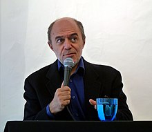 Photograph of a man, Pierre Assouline, seated with a microphone in his hand.