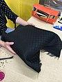Pose du tissus final sur une galette par un tapissier du Mobilier National.jpg