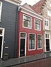foto van Eenvoudig huis met witgeverfde lijstgevel en schilddak