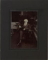 Reverend William Booth, General of the Salvation Army sitting at a small table with his left elbow resting thereon and a book resting upon his knee, opened (HS85-10-22543).jpg