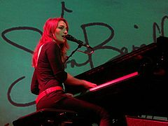 An image of an woman playing a grand piano against a teal background.