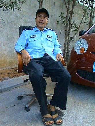Security guard - A security officer protecting the entrance to an apartment building, and managing the parking of cars in Haikou, Hainan Province, China.