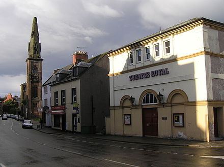 The Theatre Royal in Dumfries. In the background can be seen the spire of the old St Andrew's Cathedral: the rest of the building burned down in 1961 and was replaced with a new church on the same site. Shakespeare St, Dumfries.jpg