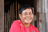 Smiling Lao woman with short hair and red shirt.jpg