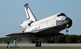 A spaceplane comes in to land at an airport runway.