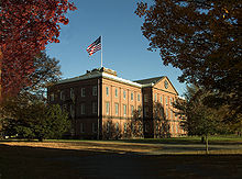 An old brick building in the Georgian architectural style surrounded by a wide lawn and trees. An American flag flies over the center of the building.