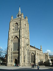 Tall ornately carved stone church with a large square tower
