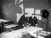 Staff officers discuss convoy movements in the Operations Room at HQ Western Approaches Command, Derby House, Liverpool, September 1944. A25742.jpg