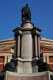 Photograph of an elaborate memorial centered on a massive stone column. At the base of the column there are two bronze statues of seated figures. There is a bronze statue of a man standing on top of the column. There are extensive carved inscriptions on the column itself. Behind the memorial is the brick and stonework facade of a large and elaborate building; there is a clear blue sky above the building.