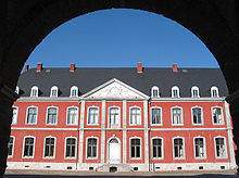 Through the archway of a gate is visible a wide part of the red-brick façade of a two-storey building, with large windows outlines with white stone arches. They grey roof shows skylight windows of a third floor. The entrance is preceded by a small set of steps and is surmounted by an ornament showing two figures supporting a coat of arms.