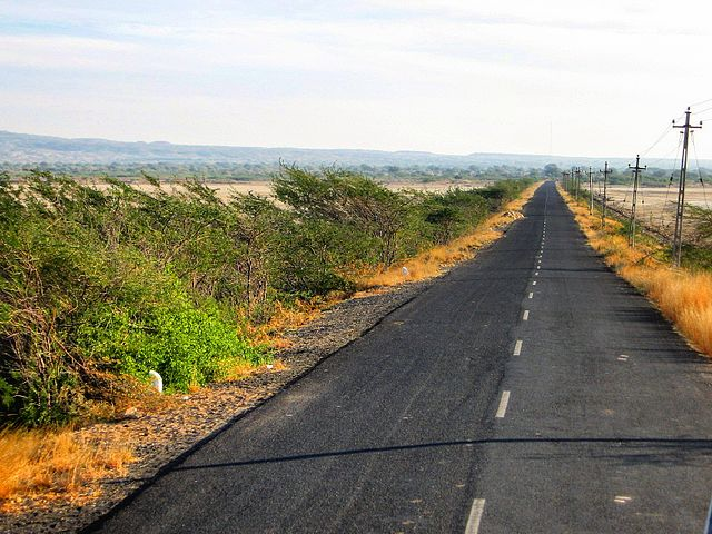 A two laned road in the Rann of Kutchh with a broken white line in the centre.