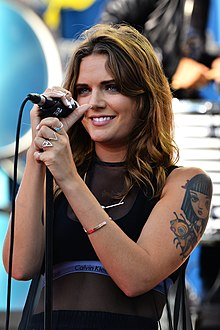A woman with brown hair wearing a black top and holding a microphone.