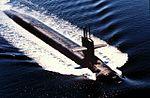 Aerial view of submarine running on surface; antennas are raised from the boat's sail.