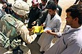 US Navy 030405-A-0000F-001 A paratrooper assigned to the 82nd Airborne Division hands out humanitarian rations to Iraqi citizens in central Iraq.jpg