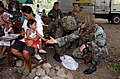 US Navy 030406-N-6501M-007 Hospital Corpsman 3rd Class Eric M. Morgan offers some treats to a Filipino child as his mother awaits treatment at the San Ramon Medical Civic Action Project (MEDCAP).jpg