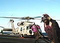 US Navy 040308-N-8704K-001 An Aviation Boatswain's Mate drags a fuel hose away from an SH-60F Seahawk assigned to the.jpg