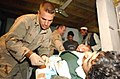 US Navy 040511-A-0000M-001 U.S. Navy Hospital Corpsman 3rd Class Chris Dare cares for a young Afghan man with kidney stones who came to the Special Forces medical clinic in the Konar province.jpg
