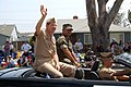 US Navy 070519-N-9706M-003 Purple Heart recipient Hospital Corpsman 2nd Class Ivan H. Delfin sits next to Commander, Navy Region Southwest Rear Adm. Len R. Herring who waves to the crowd lining the streets near the grandstand.jpg