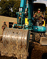US Navy 080104-N-0807W-004 Equipment Operator 2nd Class Derek Perez, assigned to Naval Mobile Construction Battalion (NMCB) 5, Detachment Sasebo, operates a backhoe to shift soil into a foundation site before laying concrete.jpg
