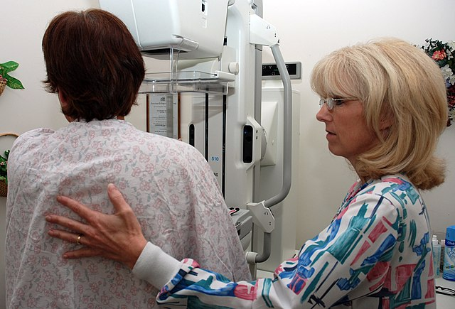 US Navy 080922-N-2688M-004 Lead Mammography Technologist Carmen Waters assists a patient
